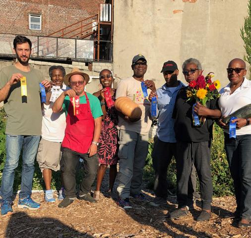 Garden members display the ribbons won at the 2019 GreenThumb Harvest Fair, a citywide event.