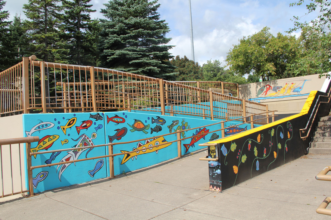 3 completed walls at the mural maze site, depicting Anishinaabe water creatures, Ojibwe florals revitalized from moccasins at the MN Historical Society, and the pictograph Chief Buffalo used on his journey to White House.