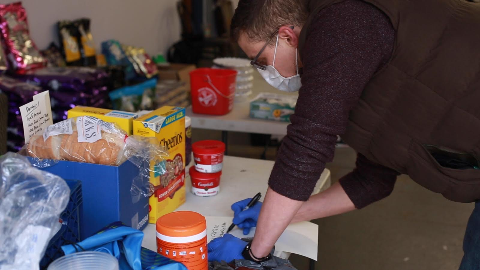 A volunteer assembles a grocery care package for workers in need.