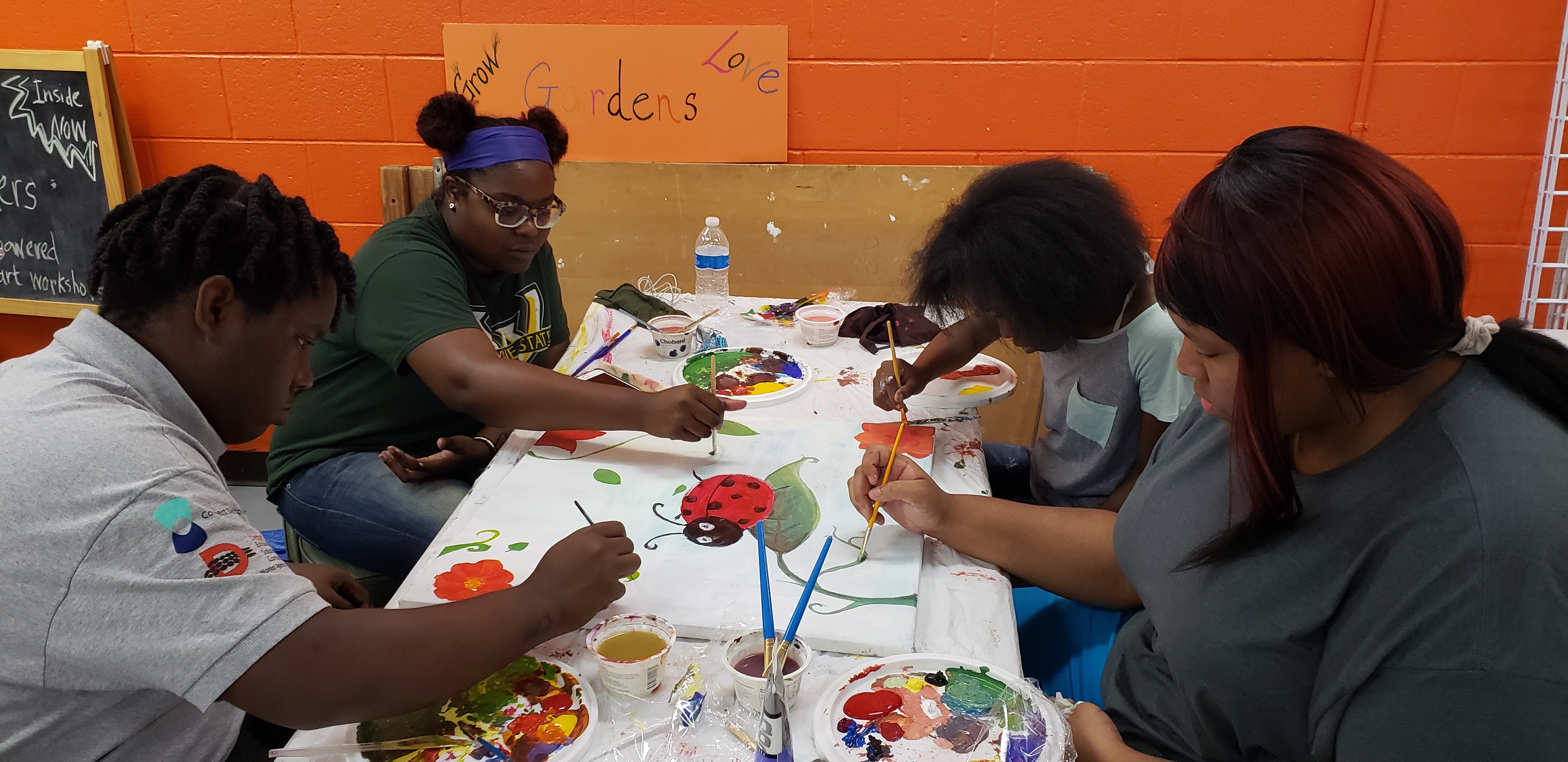 Mint summer workers learn teamwork as they work together on a nature and ladybug painting.