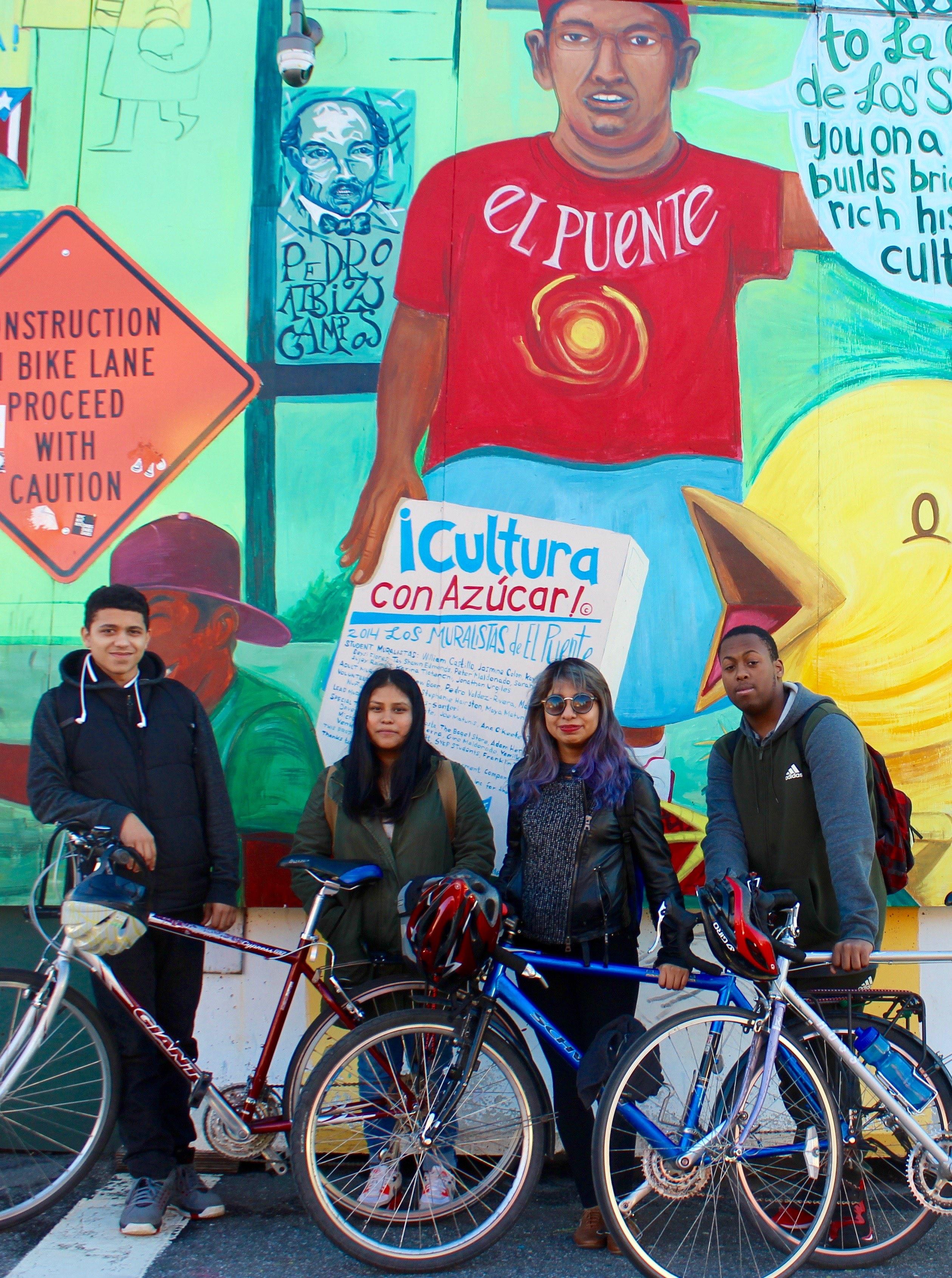 Members of El Puente Cycling Club with the mural Cultura con Azucar!