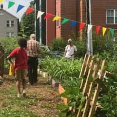 Three people standing and walking around the community garden