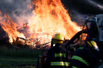Image of large fire with firefighters in foreground.