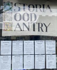 The food pantry window with signs in English, Spanish, Arabic, Greek, and Chinese