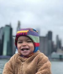 [photo of baby asylum seeker with the city in the background]
