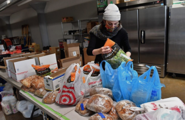 A distribution center volunteer sorts donated produce into packages on a table.