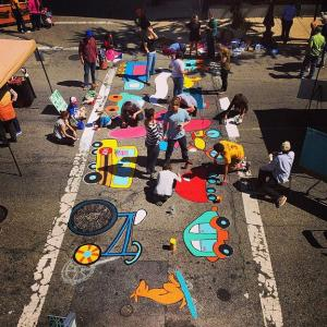 Residents gather to paint a crosswalk with an artist created, resident inspired design.