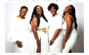 Image of 4 black women in all white laughing and smiling